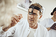 Doctor wearing surgical headlight examining patient - MFF002296