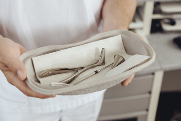 Nurse holding bowl with medical instruments - MFF002317