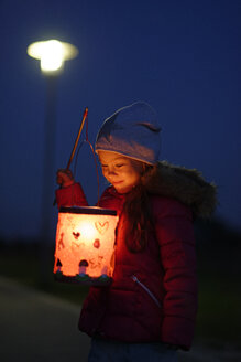 Smiling little girl with self-made paper lantern in the evening - LBF001246