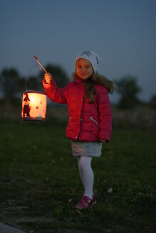 Portrait of smiling little girl with lighted paper lantern on St. Martin's Day at twilight - LBF001247