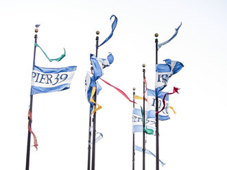 USA, San Francisco, Pier 39 flags blowing in the wind - SBDF002330