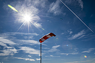Windsock against the sun with paraglider in background - FRF000342