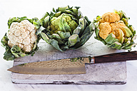 Cauliflowers, green, orange and white with knife on chopping board - SBDF002344