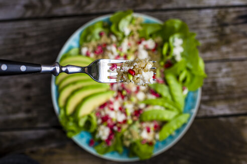 Quinoa salad with feta, pomegranate, avocado and snow peas on plate - SARF002211