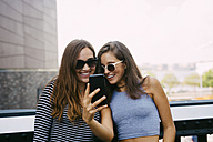 USA, New York City, two smiling friends looking at cell phone - GIOF000280