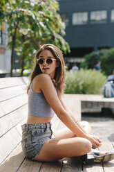 Brunette young woman wearing sunglasses relaxing on bench - GIOF000295