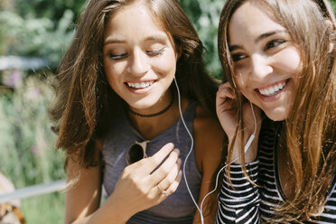 Two happy friends sharing earphones - GIOF000298