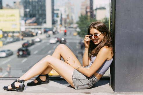 USA, New York City, smiling young woman relaxing in the city - GIOF000301