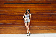 Smiling brunette young woman leaning against wooden wall - GIOF000307