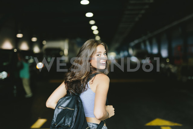 Smiling woman with a backpack ready to enter into a parking lot - GIOF000313