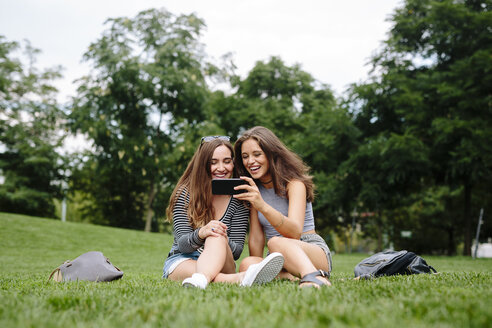 Two happy friends in a park looking at cell phone - GIOF000316