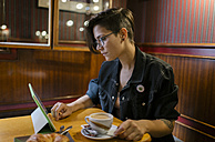Young woman sitting in a coffee shop using digital tablet - MGOF000845