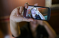 Photo on display of a smartphone of young woman taking a selfie - MGOF000848