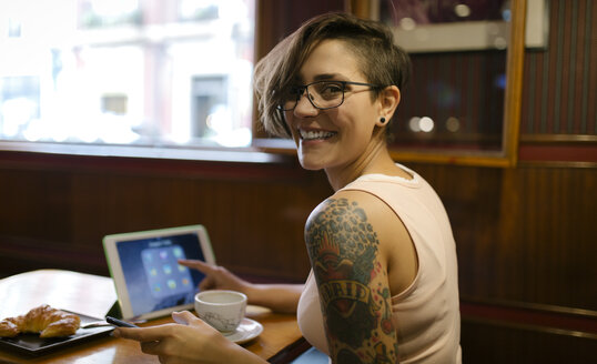 Portrait of tattooed young woman sitting in a coffee shop using digital tablet - MGOF000851