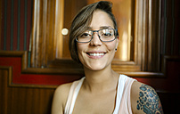Portrait of smiling tattooed young woman wearing glasses - MGOF000854