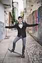 Elegant young man on skatebaord keeping the balance - RAEF000545