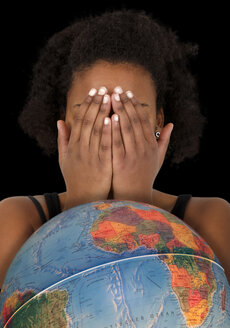 Young woman hiding her face behind globe - KLR000251