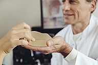 Patient feeling a silicone breast implant in doctor's hand - MFF002336