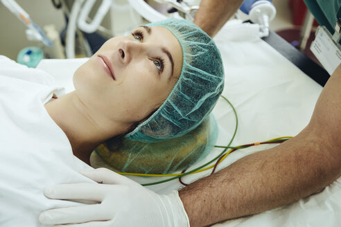 Operating nurse soothing patient on table in operating room - MFF002351