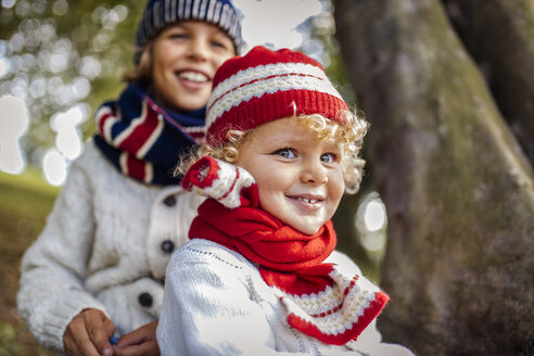 Portrait of blond little boys and his brother in the background wearing fashionable knit wear in autumn - MGOF000881