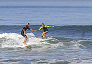 Man helping woman on surfboard - KNTF000128