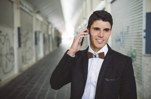 Young man on the phone wearing jacket and a wooden bow tie - RAEF000550