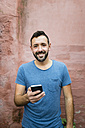 Portrait of smiling bearded man with smartphone - RAEF000556