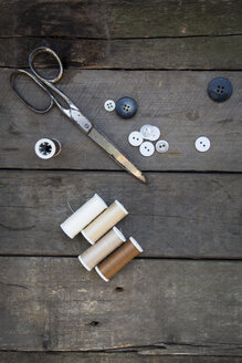 Scissors, buttons and cotton reels on wood - LVF004039