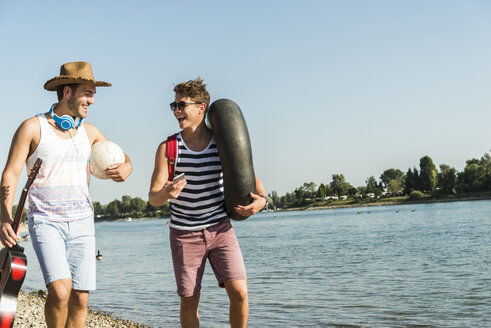 Two friends with inner tube and guitar walking at the riverside - UUF005845