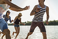 Happy friends running at the river - UUF005860