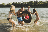 Playful friends with inner tubes in river - UUF005878