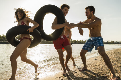 Playful friends with inner tubes by the riverside - UUF005881