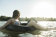 Two friends with inner tubes in water - UUF005893