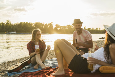 Friends relaxing at the riverside at sunset - UUF005902