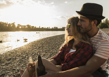 Young couple relaxing at the riverside at sunset - UUF005908