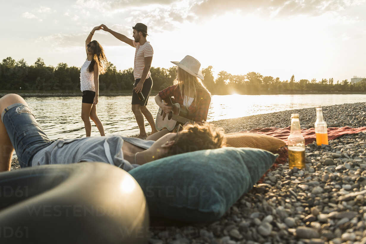 Friends relaxing at the riverside at sunset - UUF005911 - Uwe Umstätter/Westend61