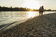 Two friends walking at the riverside at sunset - UUF005920