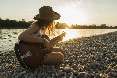 Young woman playing guitar at the riverside at sunset - UUF005926