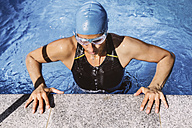 Female triathlete lifting up from pool's edge - MFF002390