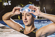 Female triathlete in swimming pool lifting goggles - MFF002399