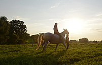 Young woman riding on horse, friend leading - BFRF001558