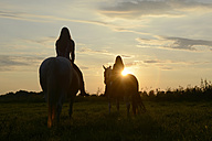 Young women riding into the sunset - BFRF001576