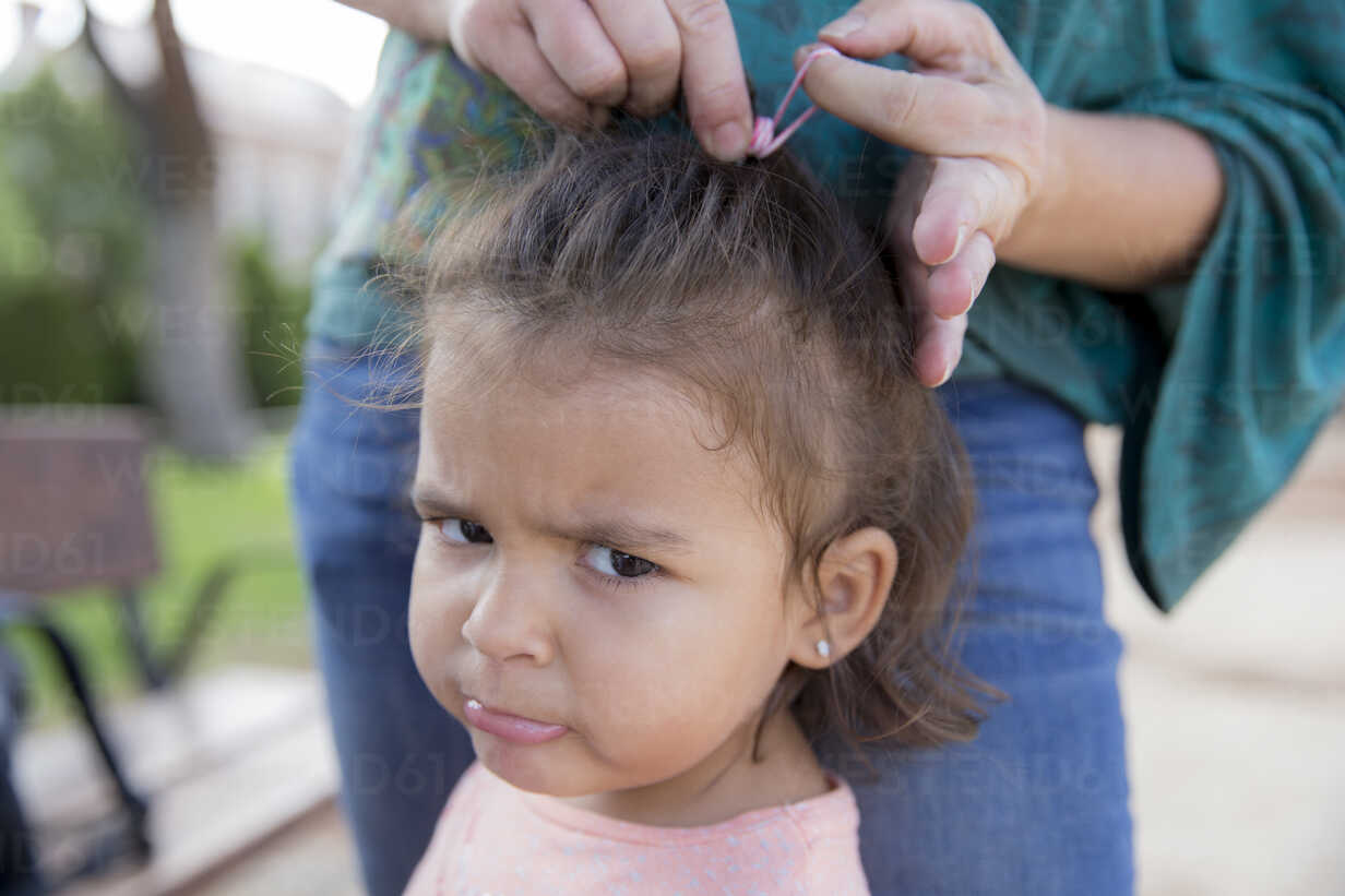 Mother tying up hair of her little daughter, close-up - ERLF000062 - Enrique Ramos/Westend61