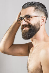 Portrait of a mid adult bare-chested man with full beard and glasses - JASF000181
