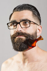 Bare-chested man with glasses and comb stuck in beard - JASF000184