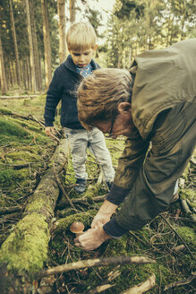 Mature man collecting porcini mushrooms with little boy - MFF002413