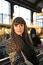 Germany, Berlin, portrait of smiling young woman waiting at platform - FKF001401