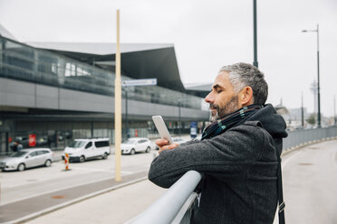 Austria, Vienna, man leaning on a railing near central station looking at his smartphone - AIF000106