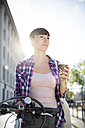 Germany, Berlin, portrait of young woman with bicycle and coffee to go at backlight - FKF001404