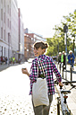 Germany, Berlin, smiling young woman with bicycle and coffee to go - FKF001419